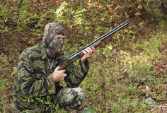 Camouflage hunter. Camouflaged hunter with a rifle kneeling in the woods Stock Photography