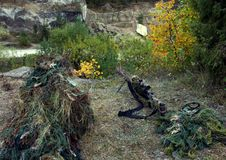 Camouflage Hunter or soldier hiding in bushes in camouflage. Autumn  background. Sniper with rifle Royalty Free Stock Photo