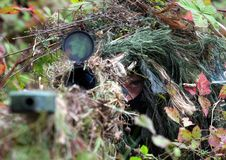 Camouflage Hunter or soldier hiding in bushes in camouflage. Autumn  background. Sniper with rifle Stock Images