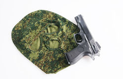 Camouflage mask and a handgun Stock Images