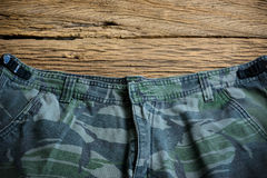 Camouflage pattern pants on wooden background Royalty Free Stock Photography