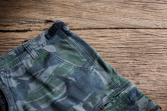 Camouflage pattern pants on wooden background Royalty Free Stock Photo