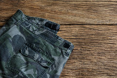 Camouflage pattern pants on wooden background Stock Photos