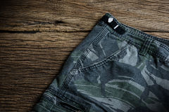 Camouflage pattern pants on wooden background Stock Photography