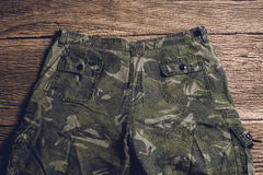 Camouflage pattern pants on wooden background Stock Images