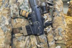 Camouflage and rifle of an armed soldier. Close up royalty free stock photos