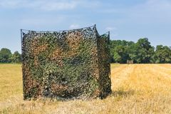 Camouflage tent in dutch grain field. For hunters or animal spotters stock images