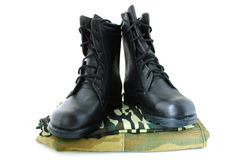 Camouflage uniform and two army boots. Camouflage uniform and black army leather boots royalty free stock photo