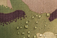 Camouflage waterproof fabric. Rain water droplets on camouflage waterproof fabric royalty free stock image