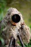 Camouflage wildlife photographer in the ghillie suit. Working in the wild Royalty Free Stock Photo