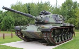 Camouflaged Army Tank. An Army tank with trees in the background. Overcast day with slight shadows Stock Photography
