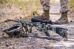 Camouflaged automatic rifle with spotting scope. Helmet,camouflaged automatic rifle with spotting scope on a background of soldier stock photography