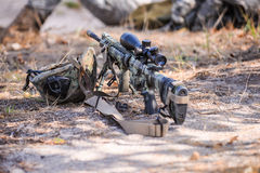 Camouflaged automatic rifle with spotting scope and helmet on gr. Sniper rifle with telescopic sight is near the helmet on the sand in forest stock photos
