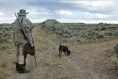 Camouflaged hunter with rifle and tracking dog. A hunter with rifle wearing camouflage following a tracking dog in a semi arid landscape in southwest Wyoming Royalty Free Stock Photo