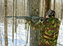 Camouflaged hunter in winter woods stock photography