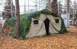Camouflaged military tent at the park Royalty Free Stock Images