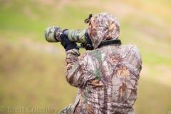 Camouflaged photographer using camera Stock Photography
