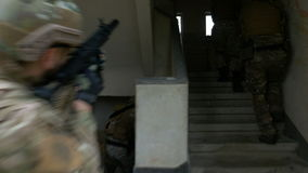Camouflaged soldiers that are walking in an abandoned building with weapons during an operational exercise stock video footage