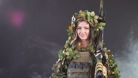 Camouflaged woman sniper in ghillie suit posing with rifle in foggy night. Special Weapons and Woman Concept stock footage