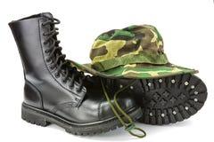 Camouflagehoed en militaire laarzen stock afbeelding