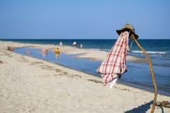 Camouflagehoed en plaidoverhemd op een pool tegen de achtergrond van een kustlijn royalty-vrije stock afbeeldingen