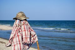 Camouflagehoed en plaidoverhemd op een pool tegen de achtergrond van een kustlijn stock foto's