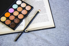 Camouflagestift, samenstellingsborstel, open boek royalty-vrije stock fotografie