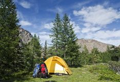 A camp. The tent, two backpacks and two pairs boots near a tourist track in mountains Royalty Free Stock Photo