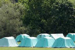 Camp. A row of blue tents on a green field with trees in the background Stock Photos