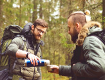 Camp, adventure, traveling and friendship concept. Man with a backpack and beard and his friend hiking in forest. Autumn color and hipster filter royalty free stock image