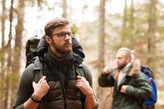Hiking in forest. Camp, adventure, traveling concept. Camp, adventure, traveling and friendship concept. Man with a backpack and beard and his friend hiking in royalty free stock photo