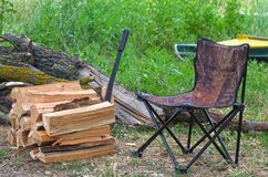 Camp chair, firewood, machete and kayak on grass background. In the forest near river; Preparation for the relax at the campfire; Lifestyle of a tourist; Scene stock images