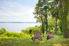 Camp Chairs. Two empty camp chairs by a secluded lake Royalty Free Stock Photo
