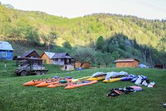 Camp des alliages et des kayaks de l'eau séchant sur l'herbe dans le village carpathien sur le fond des montagnes photo stock