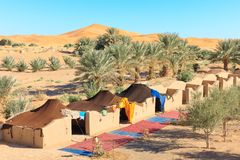 Camp in desert. A bedouin camp against one of the huge orange sand dunes in Erg Chebbi, Morocco Stock Image