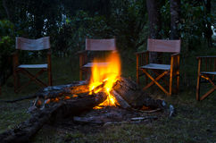Camp fire. Chairs arranged around a burning camp fire stock images