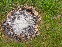 Camp Fire Ashes. The remains of a camp fire, with embers and ashes surrounded by a ring of stones Stock Image