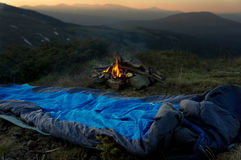 Camp fire beside lake and mountains. Royalty Free Stock Photo