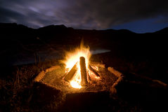 Camp fire beside lake and mountains royalty free stock photo