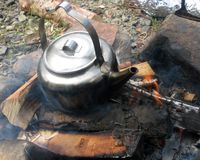 Camp fire with old kettle Stock Photo