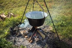 Camp fire outdoors burning with pot Stock Image