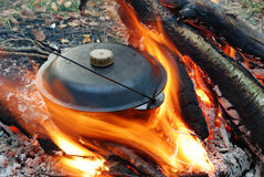 Camp fire and pot. Camp fire and cooking in steel pot stock images