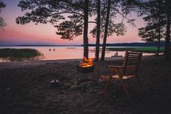 Camp fire on sandy beach, beside lake at sunset. royalty free stock image