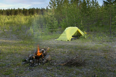 Camp fire and tourist tent. In the background Royalty Free Stock Photo