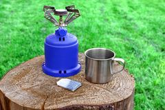 Camp Gas  Stove and steel tea mug. Royalty Free Stock Photo