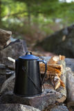 Camp Kettle. A coffee pot or water kettle sitting on a rock near the fire at a wilderness campsite royalty free stock photography