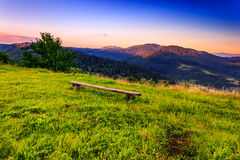 Camp in the mountains. Wooden bench on the lawn of the high mountains in the early morning Royalty Free Stock Image
