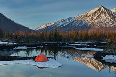 Camp near the mountain lake. Landscape with a tent near the water. royalty free stock photo