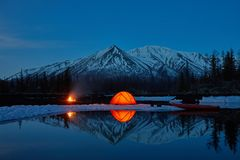 Camp near the mountain lake. Night landscape with a tent near the water. stock photo