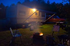 Camp at Night. A travel trailer, campfire, truck, and lawn chairs shot at night stock images
